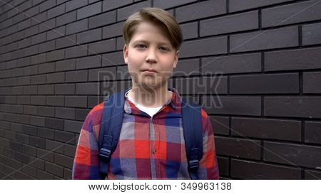 Positive Boy With Rucksack Near Wall, Excellent Student, Successful School Year