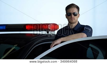 Professional Police Officer Monitoring Road Standing Near Door Of Patrol Car