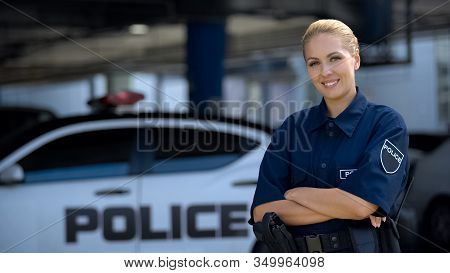 Woman Police Officer Smiling, Standing Near Patrol Car With Crossed Hands, Law