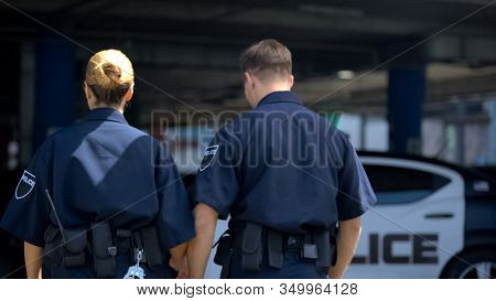 Two Police Officers Walking To Car, Patrolling District Together, Back View