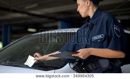 Female Cop Putting Traffic Ticket For Parking Violation On Windshield, Fine