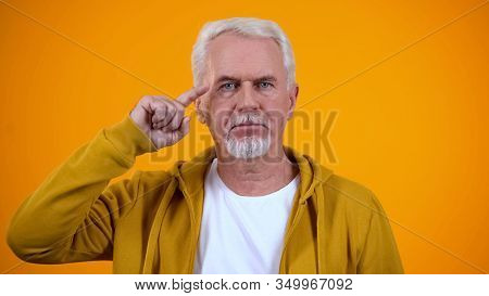 Serious Retired Male Showing Screw Loose Sign On Camera, Nonsense Or Absurd