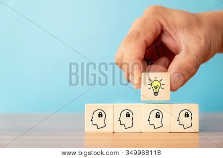 Business Concept Of Creative Idea And Innovation. Hand Picked Wooden Cube Block With Light Bulb Icon