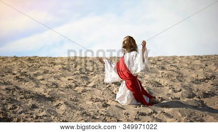 Righteous Man Kneeling In Desert, Praying To God With Raised Hands, Confession