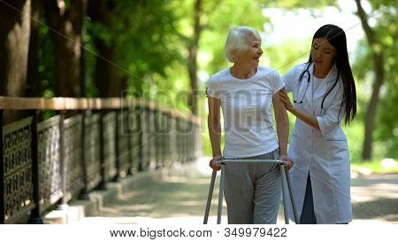 Caring Nurse Helping Senior Disabled Woman With Frame Walk In Park, Rehab