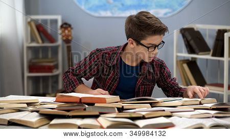 Hardworking Male Teen Searching Information Sitting Table Full Of Books, Student