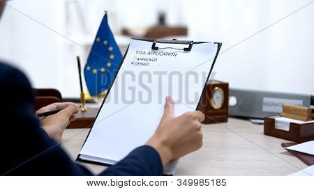 Immigration Inspector Denying Visa Application, European Union Flag On Table