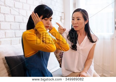 Argument Between Annoyed Asian Teenage Daughter And Upset Middle Aged Mother. The Child Covering Ear
