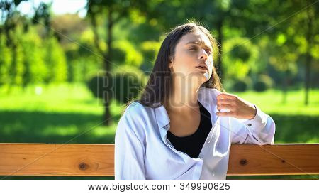Young Woman Resting On Bench In Park Suffering From Heat And Stuffiness, Pms