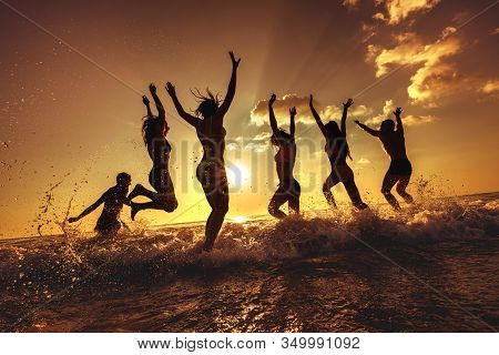 Big Group Of Happy Young Friends Are Having Fun At Sunset Sea Beach, Run And Jump Over Waves