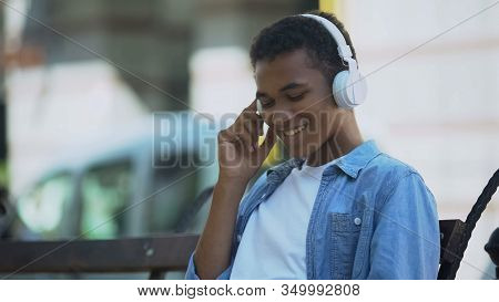 Positive Young Man Listening To Music In Headphones, Sitting On Bench Outdoors