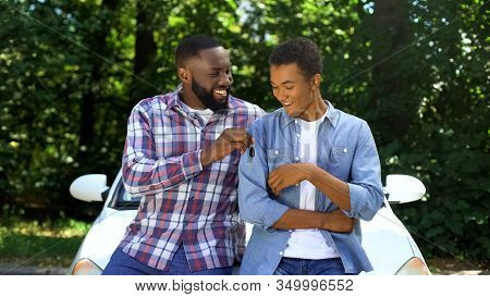Happy Dad Giving Car Key To Son, Permission To Drive, Parenthood Trust, Family