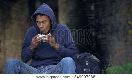 Starving Troubled Teen Chewing Snack Sitting Outdoors, Dangerous City Suburb