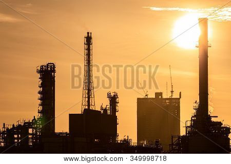 Silhouette Of Oil And Gas Refinery Industry Plant With Glitter Lighting And Sunrise In The Morning,