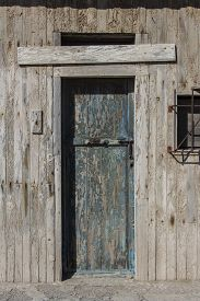 Old Wooden Door With Traces Of Blue Paint, Old Wooden Door Of A Warehouse Or A Barn, Old Gate Made O
