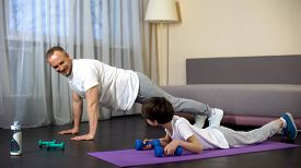 Serious Sportive Family Doing Plank Exercise With Dumbbells At Home, Role Model