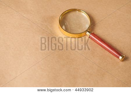 Magnifying Glass On Brown Background