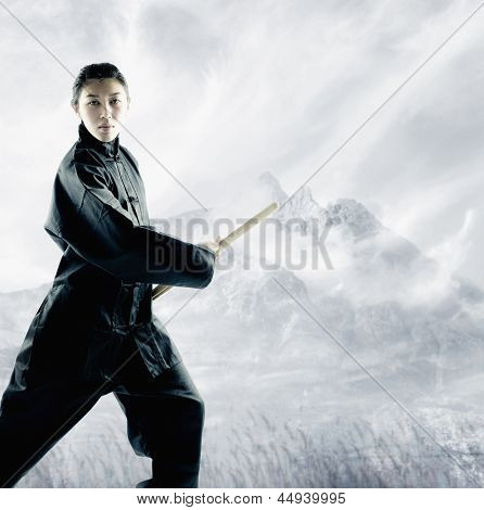 Portrait of a young woman holding a shinai standing in a martial arts stance
