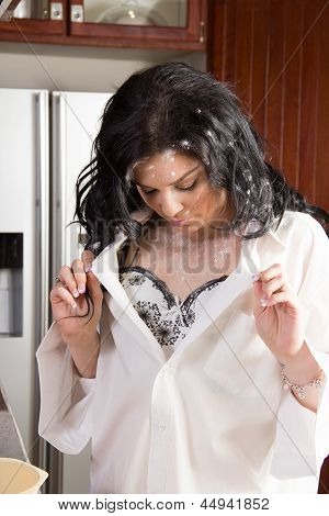 Young Woman In Kitchen Looking At The Spilled Flour On Her