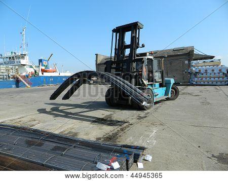 a dockside forklift moving steel into storage