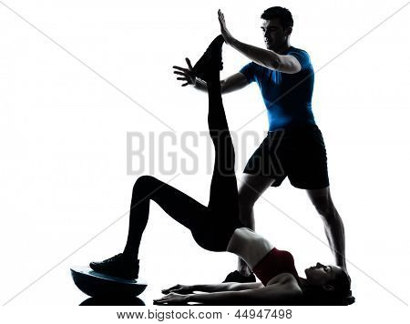 personal trainer man coach and woman exercising abdominals push ups on bosu silhouette  studio isolated on white background poster