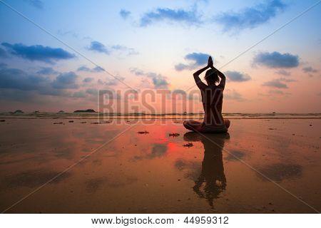 Junge Frau Silhouette praktizieren Yoga am Strand bei Sonnenuntergang