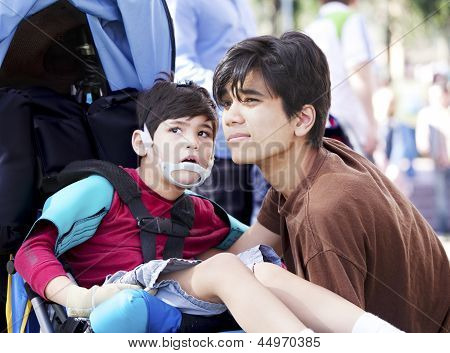 Big brother taking care of disabled little boy in wheelchair outdoors. Child has cerebral palsy. poster