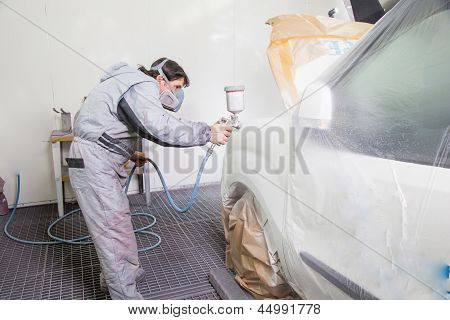 Car body painter spraying paint or color on bodywork in a garage or workshop with an airbrush poster