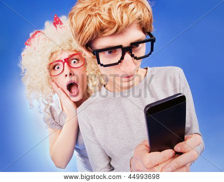 Girl is spying on boyfriend he is using a smart phone