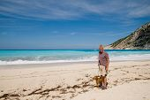 retired man with his dog at the tropical beach poster