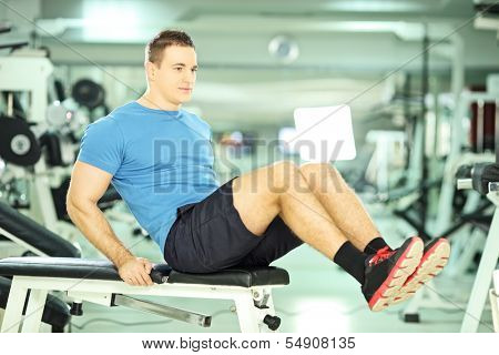 Young man seated on a bench exercising abdominal muscles in a fitness club