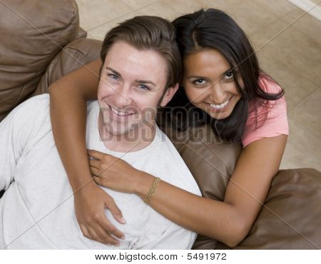A young attractive couple relaxing on the couch poster