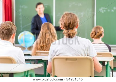 Teacher or educator or docent standing while lesson  in front of a blackboard and educate or teach students or pupils or mates in a school or class