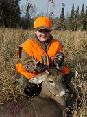 A young deer hunter with a Whitetail Deer poster