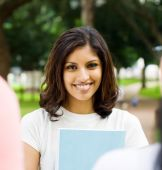 Portrait of a happy beautiful indian college student, she is facing her classmates poster