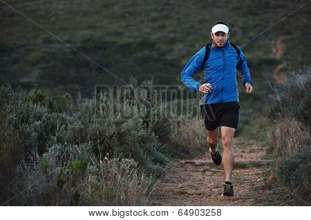 ultra marathon trail runner training in mountains for fitness and exercise wearing windbreaker poster