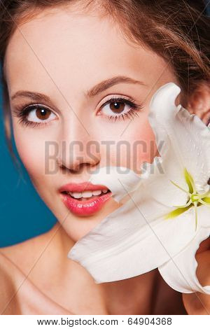 The face of a beautiful girl with fresh flower lily