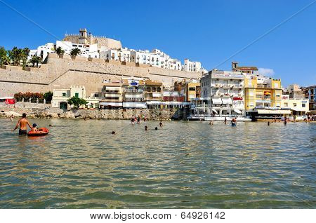 PENISCOLA, SPAIN - JULY 26: Bathers in North Beach, facing the castle, on July 26, 2013 in Peniscola, Spain. The town is a typical summer destination in the North of the Valencian Community