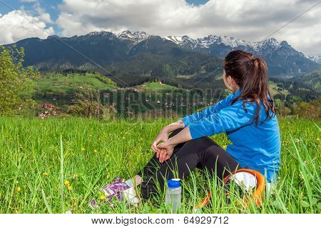 Hiking young woman resting in the top of the mountain watching the amazing view poster