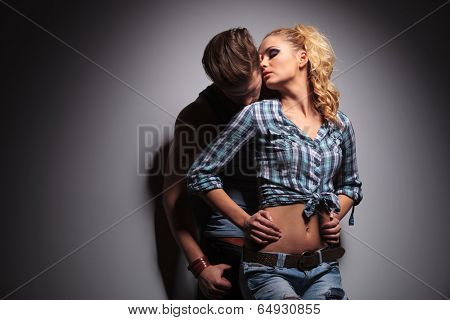 passionate casual young couple standing embraced in studio