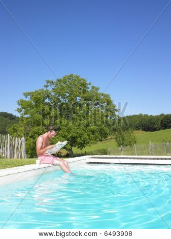 Man Reading At Edge Of Swimming Pool