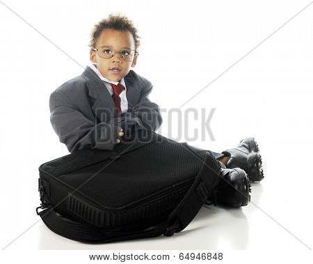 An adorable tot sitting with his computer case while dressed in an oversized business suit and dress shoes.  On a white background.