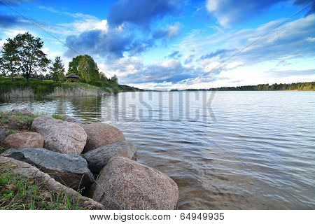 Bank of the lake with stones and summerhouse