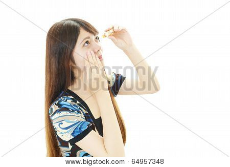 Tired woman with eyes drops