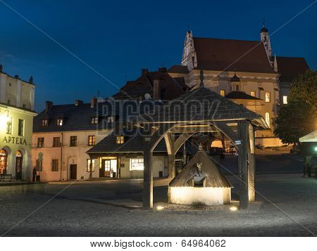 Kazimierz Dolny town square by night with historical wooden well in the center, Poland