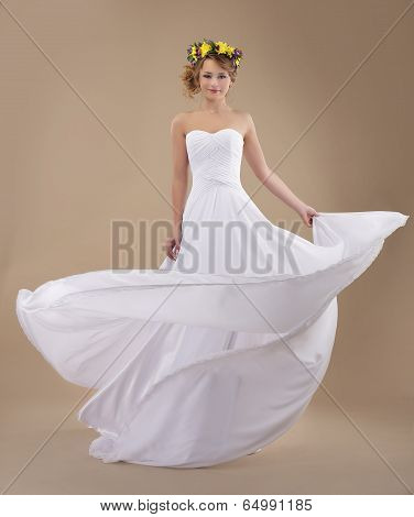 Motion. Woman With Wreath Of Flowers And Fluttering Light Dress
