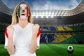 Excited mexico fan in face paint cheering against large football stadium with brasilian fans poster