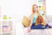 Beautiful young woman with cocker spaniel on couch in room poster