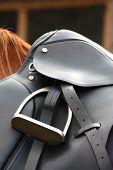 Close up of black leather saddle on horse back poster