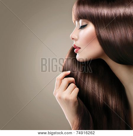 Beauty Model girl with Healthy Brown Hair. Beautiful woman touching her long smooth shiny straight hair. Hairstyle. Hair cosmetics, haircare